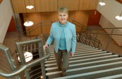 Nancy Straw in a turquoise jacket walks up the stairs the Foundation