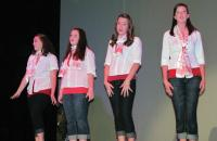 A row of women sing on stage