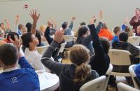 Children raise their hands while listening to an adult