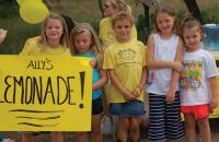 Children holding a sign advertising lemonade