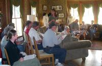 A group of people listen to a speaker in a living room