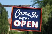 """A sign says """"Come in we're open"""""""