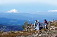 Couple sets up a tent with mountain in background