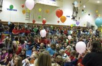 A crowd of people in an auditorium hold balloons