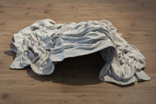 A crumpled white bedspread on a wooden floor