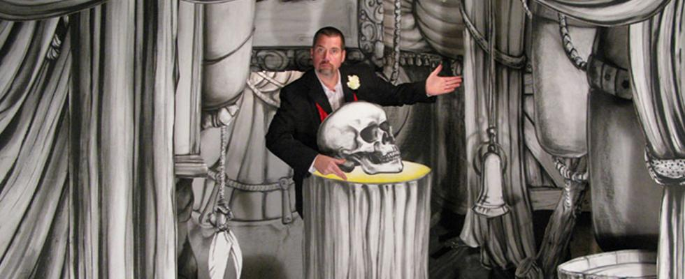 Artist Davide Eckard in a black suit stands in a black and white mural.