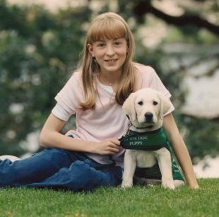 A young Maria poses on the lawn with a puppy wearing a green Guide Dogs jacket.
