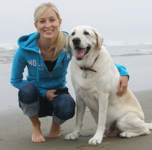 An adult Maria poses on the beach with a full grown Labrador.