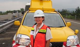 A woman wearing a hard hat stands in front of an emergency vehicle.
