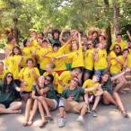 Group of about 50 children in matching yellow T-shirts