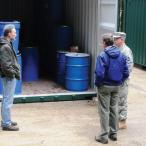 Three men inspect a large shipping container that provides storage for emergency supplies