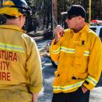 "Two firefighters, one on a walkie-talkie, converse. ""Ventura City Fire"" is emblazoned on the back of one."