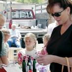 Woman looks at goods at farmers market stall.