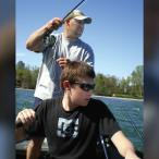 A teen-age boy rows a boat while his father fishes