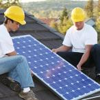 Two workers install a solar panel on a roof